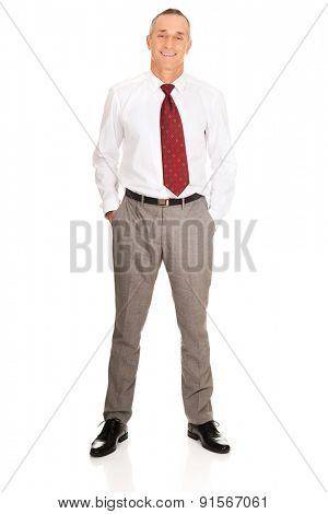 Full length mature businessman with hands in pockets.