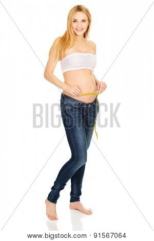 Woman measuring her growing pregnancy belly