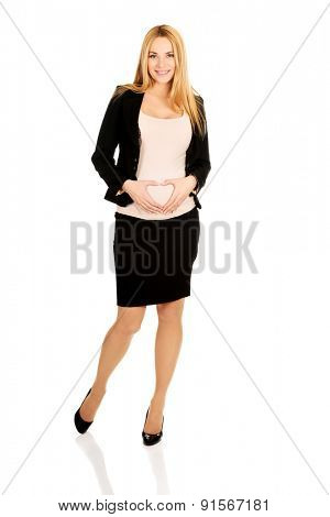 Smiling pregnant woman making heart shape on belly.