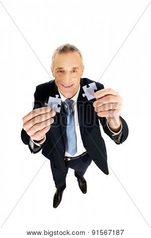 Smart mature man trying to connect puzzle pieces.