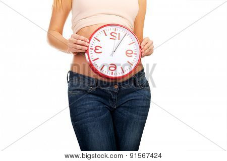 Happy pregnant woman with clock expecting baby