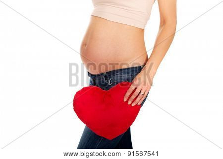 Pregnant woman with a red heart pillow