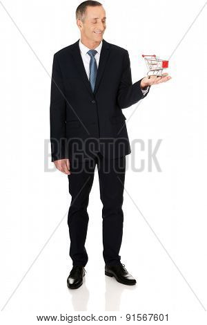 Full length businessman holding shopping cart.