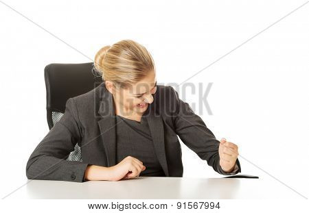 Angry businesswoman sitting at the desk.