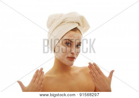 Portrait of a woman with cream lotion on face and towel on head.