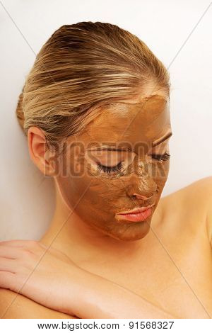 Portrait of a woman with closed eyes and chocolate mask on face .