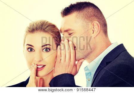 Men whispering secret to his surprised friend