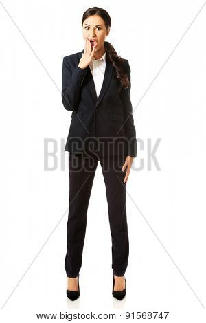 Full length shocked businesswoman covering mouth.
