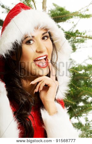 Portrait of santa woman touching mouth with christmas tree on a background.