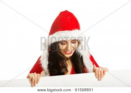 Portrait of santa woman holding white empty banner, looking down on it
