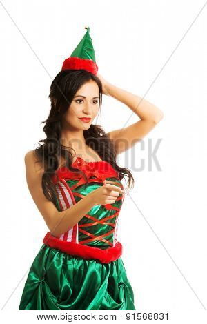 Portrait of woman wearing elf clothes pointing to the left.