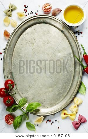 Italian food background with vine tomatoes, basil, pasta,  olive oil, chili peppers, garlic and peppercorns. Slate background.
