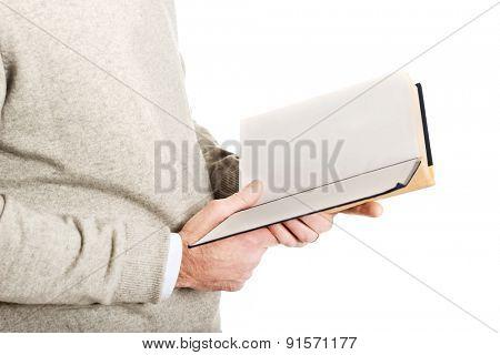 Close up on mature man hands reading a book.