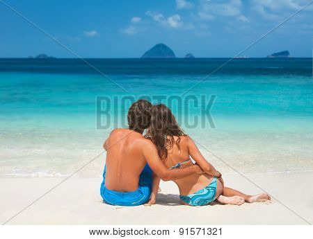 Happy Loving Couple Sitting On The Beach
