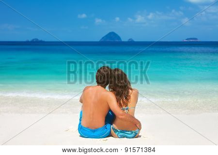 Young Couple Sitting Together On A Sandy Tropical Beach