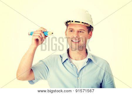 Engineer in white helmet writing on copy space with huge pencil