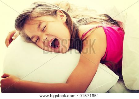 Pretty young girl yawning while waking up