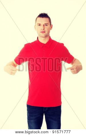 Excited man pointing on copy space on his tshirt