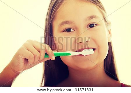 Little smiling girl brushng teeth