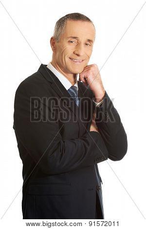 Happy mature businessman with hand under chin.