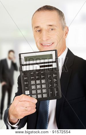 Happy businessman holding a calculator.