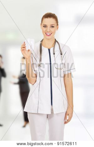 Happy female dentist holding a tooth model.