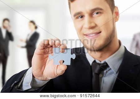 Young handsome businessman holding piece of puzzle.