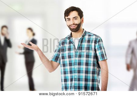 Young caucasian man showing something on palm.