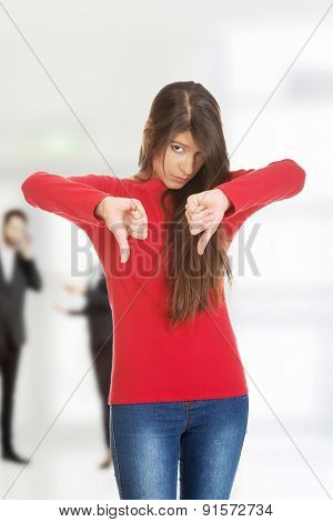Unhappy young woman with thumbs down.