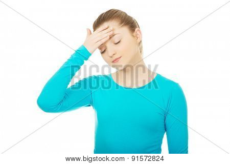 Teen woman with headache holding her head.