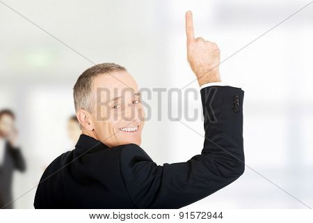 Happy mature businessman pointing upwards.