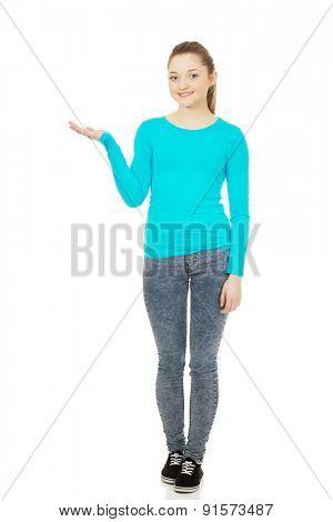 Teenage woman showing something on open hand.