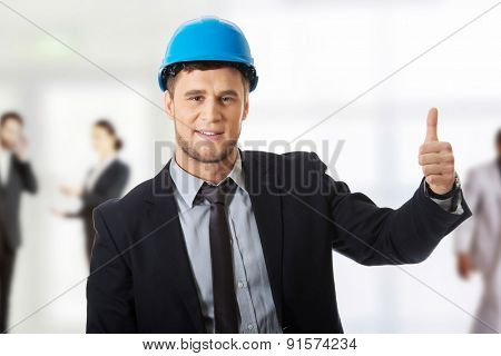 Happy businessman in hard hat with thumbs up gesture.