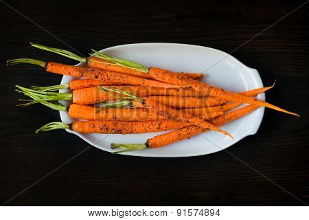 Oven-baked Baby Carrots Sprinkled With Fresh-grounded Black Pepper On White Plate On Dark Table
