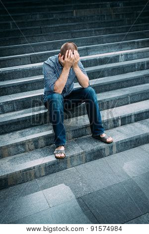Outdoor Portrait Of Despaired Young Man Covering His Face With Hands Sitting On Stairs