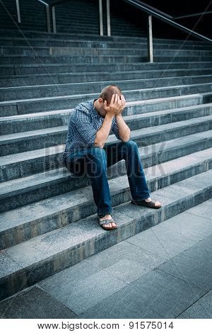 Despaired Young Man Covering His Face With Hands Sitting On Stairs Of Big Building