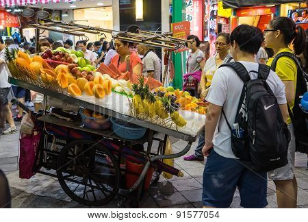A Taiwanese hawker is selling fruits on street in Xiamen