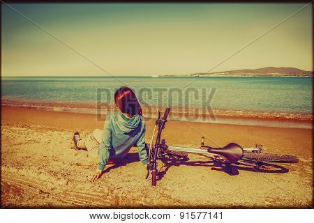 Girl With Bicycle Resting On Beach
