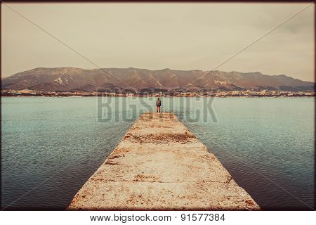 Hiker Woman Standing On Pier In Front Of Mountains