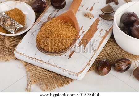 Raw Organic Ground  Nutmeg On  A Wooden Cutting Board.