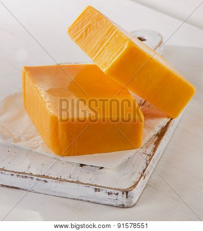 Cheddar Cheese On A White Wooden Cutting Board.