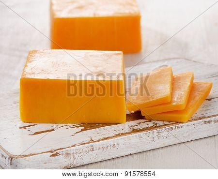 Cheddar Cheese On  Wooden Cutting Board.