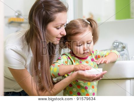 Child and mom washing hands with soap in the bathroom. Hygiene concept.