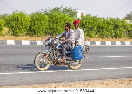 Men Riding On Scooter Through Busy Highway