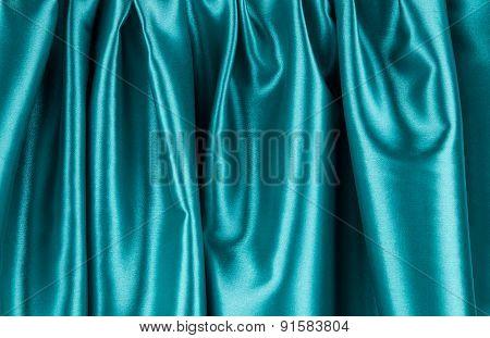 Soft folds of blue silk cloth texture.