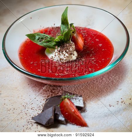 strawberry soup with ice cream and mint on a plate decoratedfresh strawberries