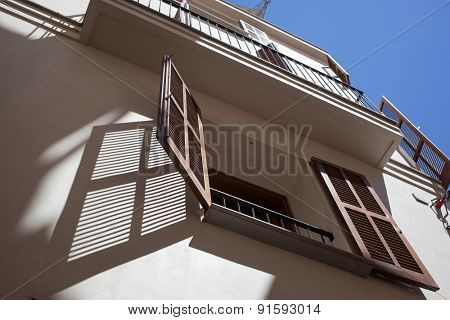 Open wooden window in hot summer day with shadow on the wall