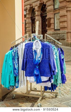 New collection of clothes hanging on a rail outside