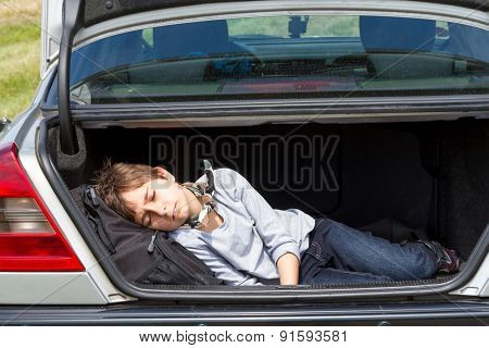 Sleeping boy in the trunk of a car