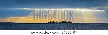 Panorama of lake sunset with sunrays coming through clouds. Lake Narach, Belarus